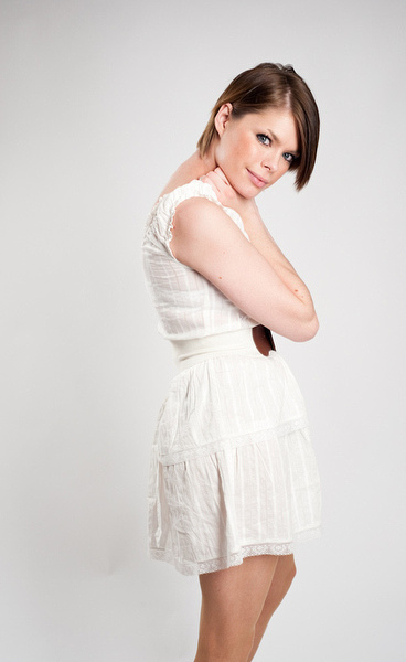 A young woman in a white dress and brown belt in studio.