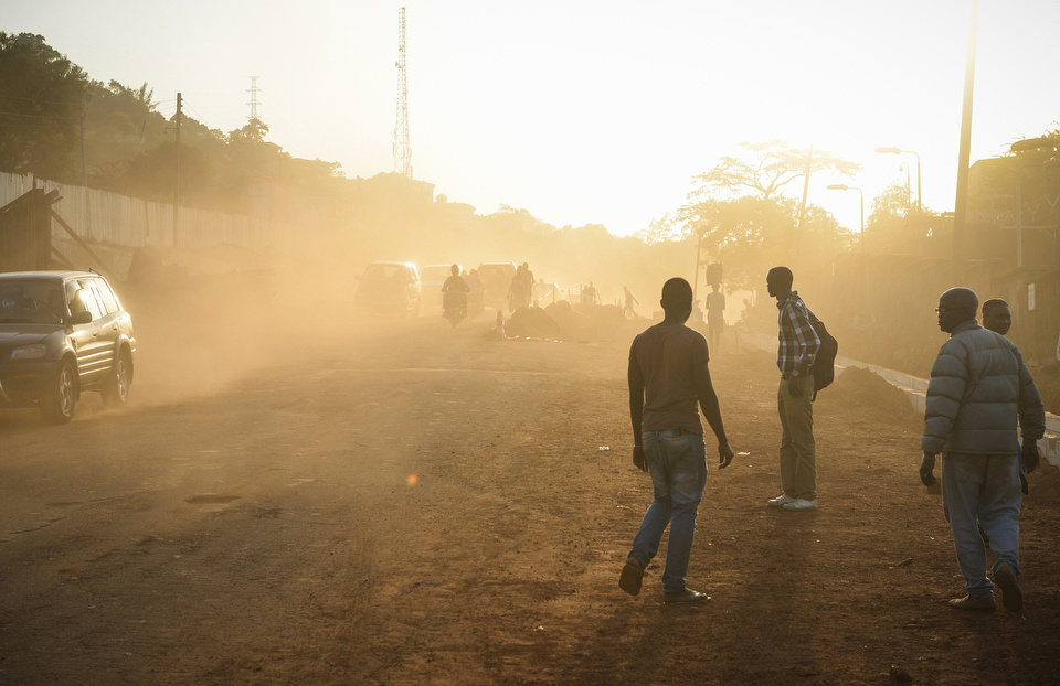 THE SUNSET BACK LIGHTS THE DUST DOWN A ROAD OUTSIDE OF THE NATIONAL EBOLA RESPONSE CENTRE (NERC) IN FREETOWN