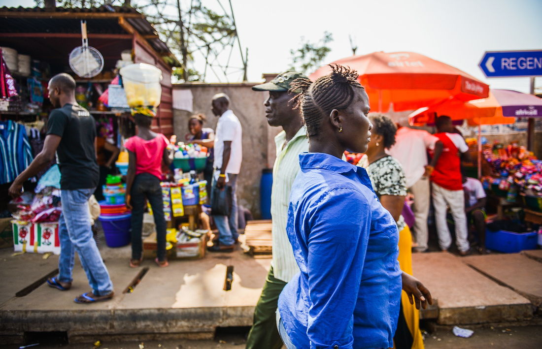 A MAN AND WOMAN PASS A BUSY MARKET ON THE SIDE OF THE ROAD