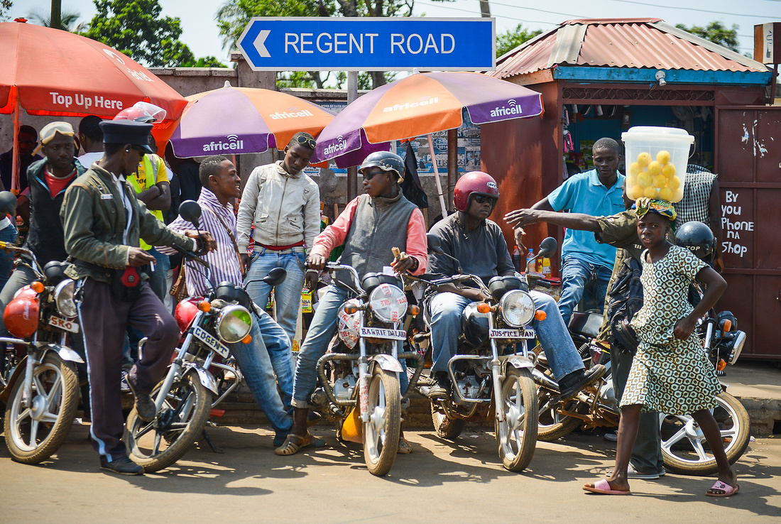 BIKES USED AS TAXIS WAIT FOR A FARE IN FRONT OF MARKET STALLS