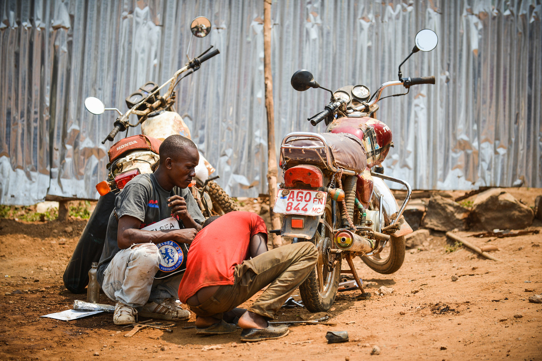 TWO MEN REPAIR A MOTORCYCLE