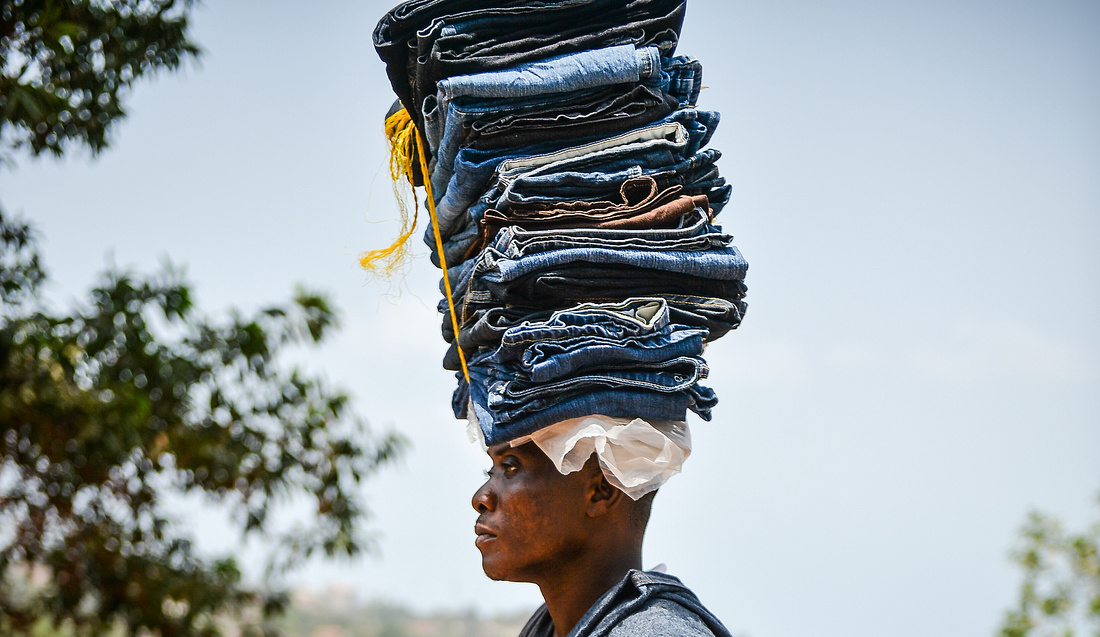 A STREET SELLER CARRYING A PARCEL OF DENIM JEANS ON HIS HEAD. THE SELLERS WALK THE STREETS SELLING THEIR GOODS.
