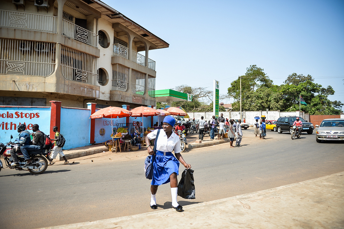 A GIRL IN A SCHOOL UNIFORM CROSSES A BUSY ROAD WHICH LEADS INTO FREETOWN