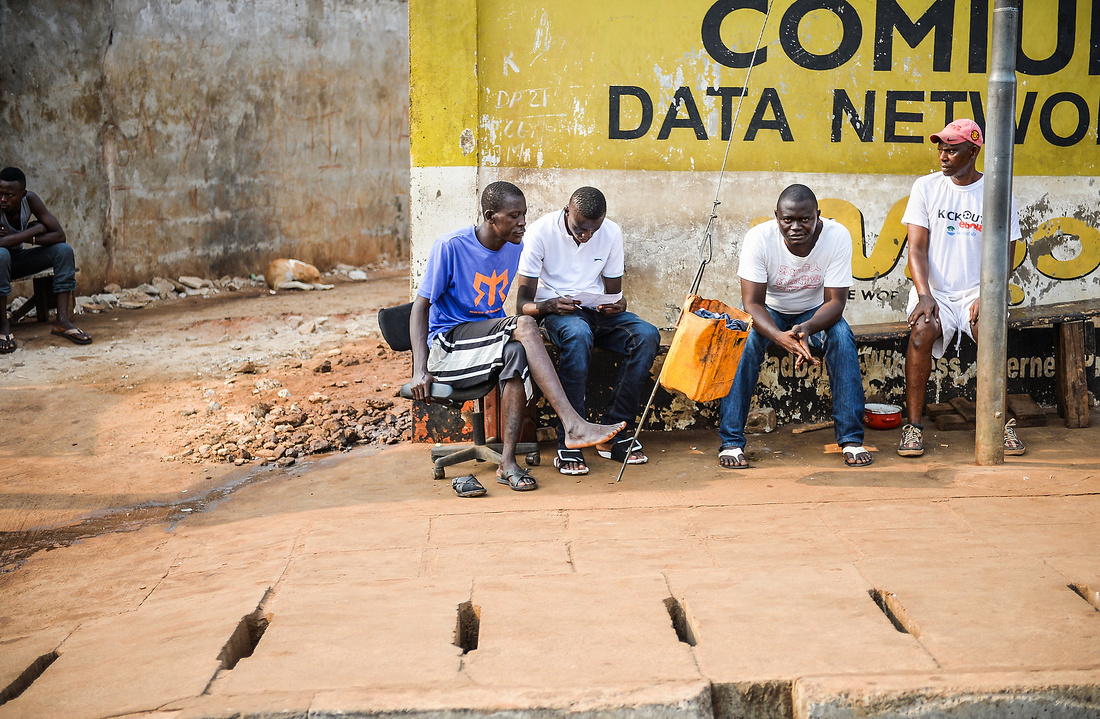 FOUR MEN SIT AT THE SIDE OF ONE OF FREETOWN'S MAIN ROADS. ONE LOOKS BACK AT THE CAMERA.