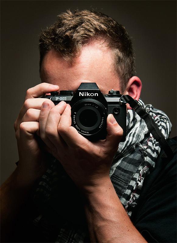 A portrait of of Tim Jones of jonesmrjones.co.uk holing a Nikon F-301.