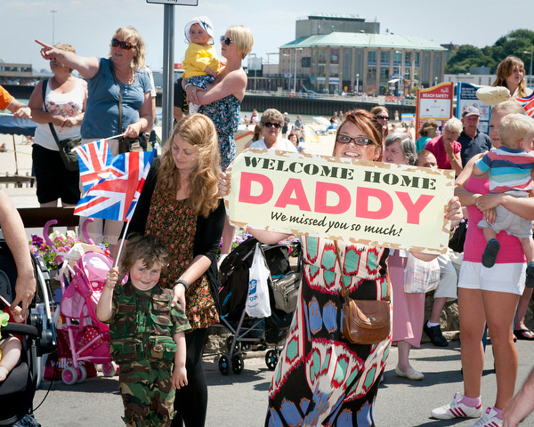 "A woman holds up a banner with the words ""Welcome Home Daddy"""
