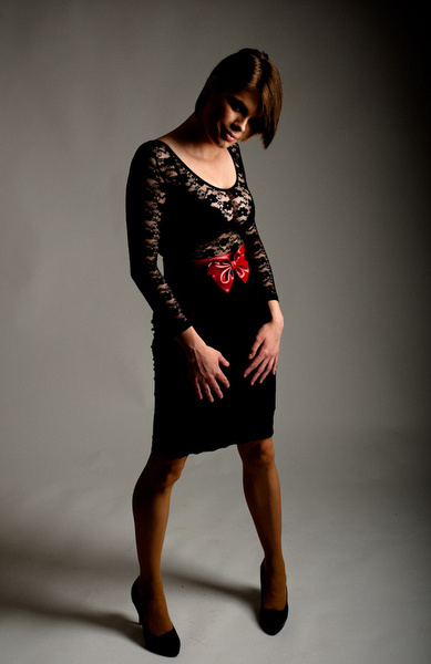 A young woman in a black net top and black skirt with red belt in studio.