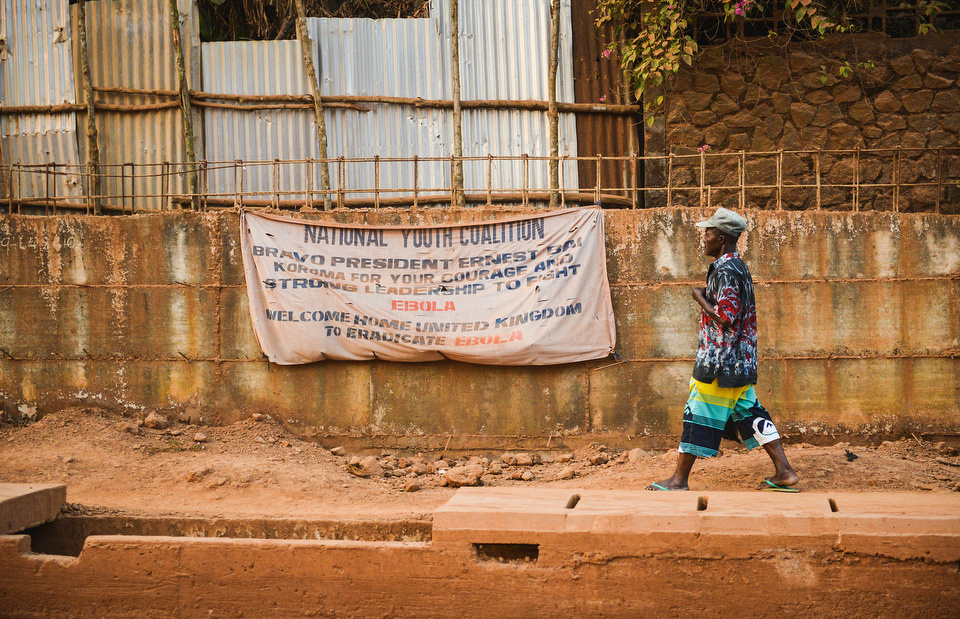 A MAN WALKS PAST A NATIONAL YOUTH COALITION BANNER