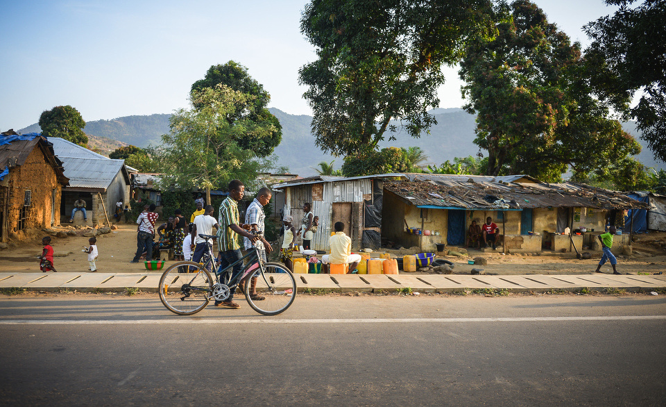 A MAN PUSHES A BICYCLE PAST A GROUP OF HOUSES AND SHACKS