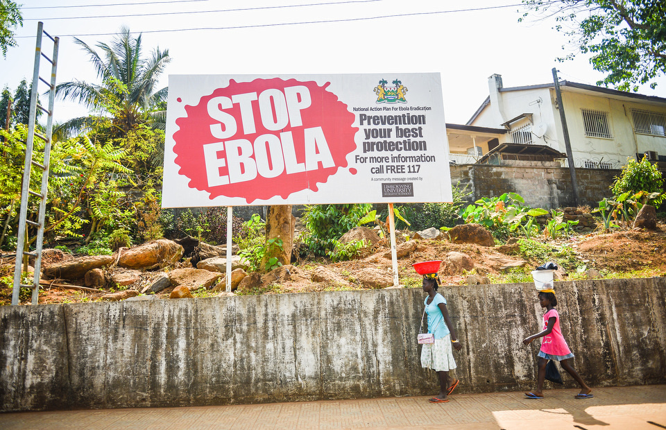 "TWO SIERRA LEONEAN FEMALES WALK PAST A SIGN WITH THE ""STOP EBOLA"" WRITTEN ON IT"
